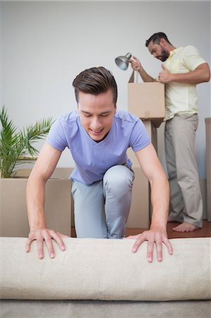 Handsome man unrolling carpet with his behind Stock Photo - Premium Royalty-Free, Code: 6109-08203688