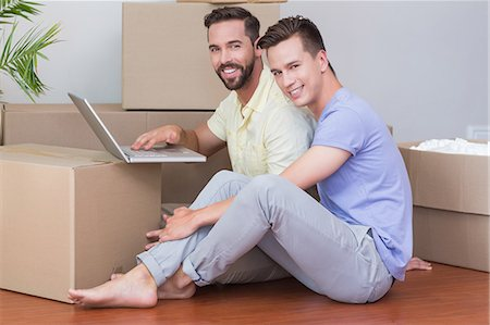Happy homosexual couple looking at camera and using laptop computer Stock Photo - Premium Royalty-Free, Code: 6109-08203692