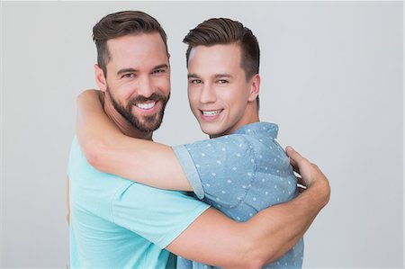 Happy homosexual couple looking at camera and hugging Stock Photo - Premium Royalty-Free, Code: 6109-08203702
