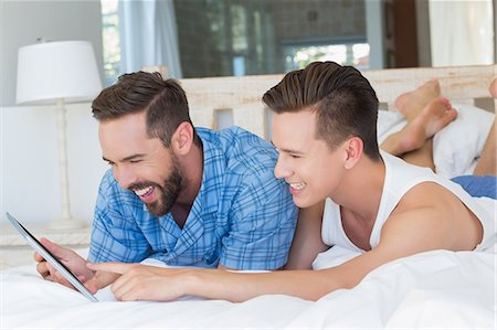 Happy homosexual couple looking at tablet computer Stock Photo - Premium Royalty-Free, Code: 6109-08203715