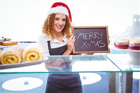 staff - Happy pretty barista holding board with santa hat Stock Photo - Premium Royalty-Free, Code: 6109-08203844