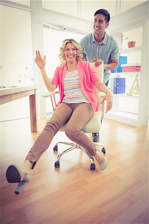 Smiling colleagues playing together with swivel chair Stock Photo - Premium Royalty-Free, Code: 6109-08203920