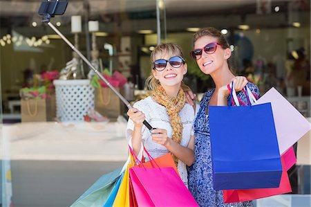 shopping mall - Beautiful women holding shopping bags making a selfie Stock Photo - Premium Royalty-Free, Code: 6109-08204126