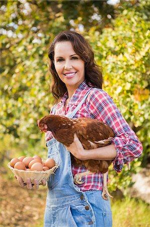 Happy brunette holding her chicken Stock Photo - Premium Royalty-Free, Code: 6109-08204271