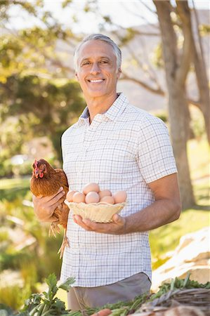 Happy farmer holding chicken and eggs Stock Photo - Premium Royalty-Free, Code: 6109-08204288