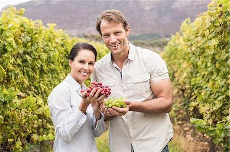 seasonal - Smiling couple showing a bunch of grapes Stock Photo - Premium Royalty-Free, Code: 6109-08204218