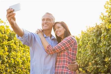 farm phone - Happy couple embracing and taking selfies Stock Photo - Premium Royalty-Free, Code: 6109-08204356