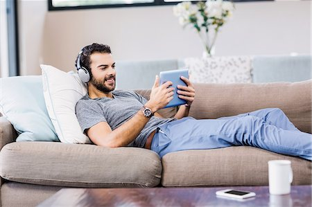 scroll - Handsome man using tablet and headphones Stock Photo - Premium Royalty-Free, Code: 6109-08390121