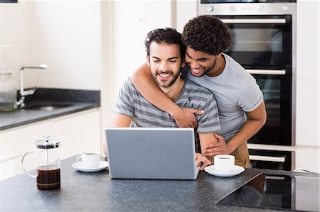 Happy gay couple using laptop on counter Stock Photo - Premium Royalty-Free, Code: 6109-08390261