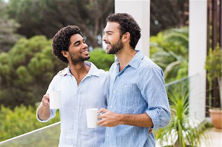 Smiling gay couple holding cups and talking Stock Photo - Premium Royalty-Free, Code: 6109-08390278