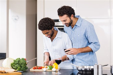 Happy gay couple drinking wine and slicing vegetables Stock Photo - Premium Royalty-Free, Code: 6109-08390293