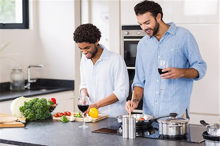 Happy gay couple drinking wine and cooking Stock Photo - Premium Royalty-Free, Code: 6109-08390295