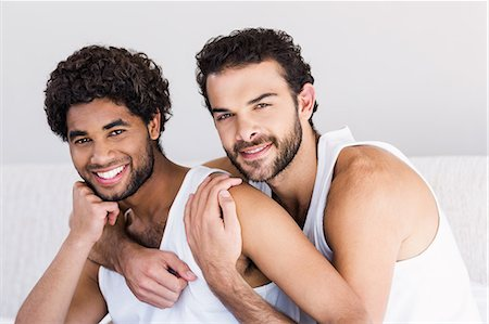 Smiling gay couple hugging on bed Stock Photo - Premium Royalty-Free, Code: 6109-08390399