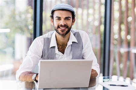 professional (pertains to traditional blue collar careers) - Smiling man using laptop Stock Photo - Premium Royalty-Free, Code: 6109-08390321