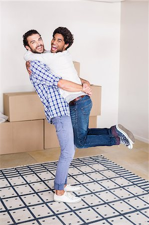 Happy gay couple hugging in new house Stock Photo - Premium Royalty-Free, Code: 6109-08390471