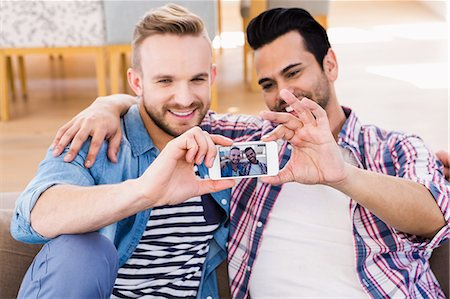 Gay couple relaxing on the couch taking selfie Stock Photo - Premium Royalty-Free, Code: 6109-08390567