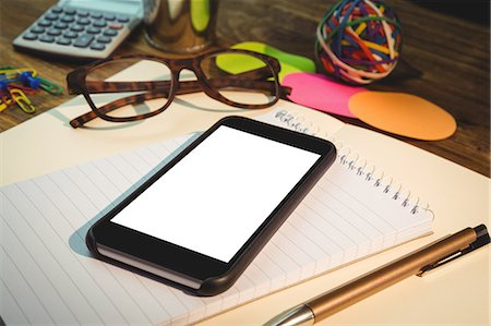 planner - High angle view of mobile phone on notepad Stock Photo - Premium Royalty-Free, Code: 6109-08395091