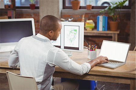 Cartoonist working on laptop besides computer Stock Photo - Premium Royalty-Free, Code: 6109-08395503