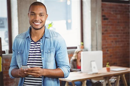 professional (pertains to traditional blue collar careers) - Portrait of smiling man using phone at office Stock Photo - Premium Royalty-Free, Code: 6109-08395680
