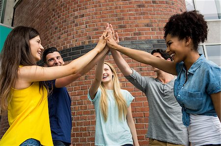 Students putting hands together in unity Stock Photo - Premium Royalty-Free, Code: 6109-08396016