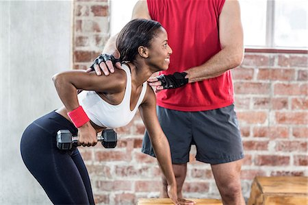 equipment - Muscular woman lifting dumbbell with her trainer Stock Photo - Premium Royalty-Free, Code: 6109-08396872
