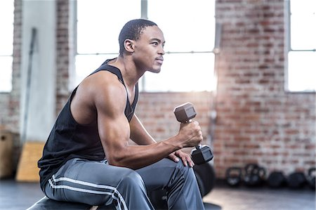 Muscular man doing dumbbell exercises Stock Photo - Premium Royalty-Free, Code: 6109-08397113