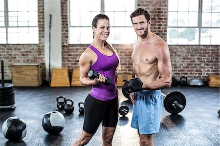skinny man muscle pose - Fit couple posing with dumbbells Stock Photo - Premium Royalty-Free, Code: 6109-08397129