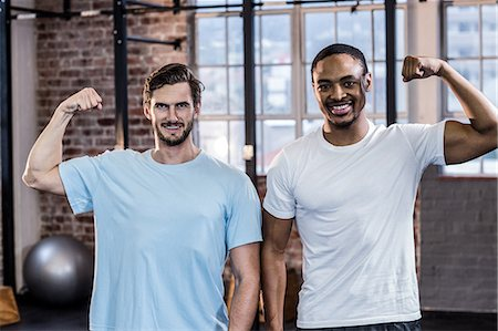 Two muscular men flexing biceps Stock Photo - Premium Royalty-Free, Code: 6109-08397219