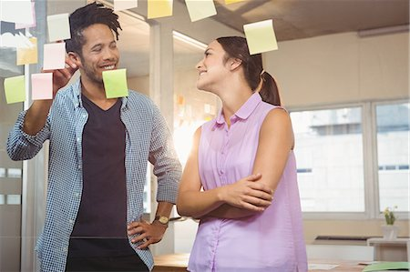 self adhesive note - Creative businessman smiling and pointing at sticky notes Stock Photo - Premium Royalty-Free, Code: 6109-08397373