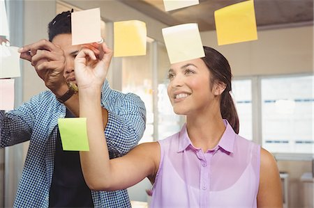Business people smiling and working on sticky notes Stock Photo - Premium Royalty-Free, Code: 6109-08397379