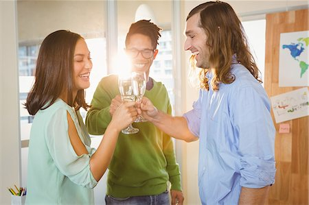 Business people toasting during celebration in creative office Stock Photo - Premium Royalty-Free, Code: 6109-08397432
