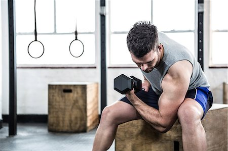 Fit man lifting heavy black dumbbell Stock Photo - Premium Royalty-Free, Code: 6109-08397753