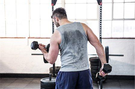 Fit man lifting heavy black dumbbells Stock Photo - Premium Royalty-Free, Code: 6109-08397769