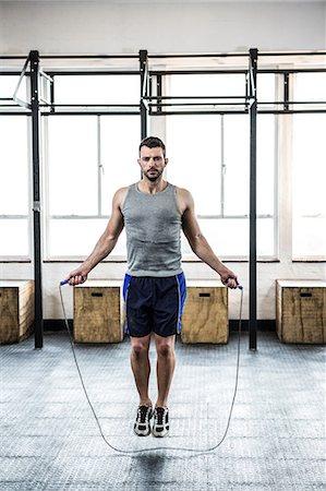 Fit man using skipping rope Stock Photo - Premium Royalty-Free, Code: 6109-08397776