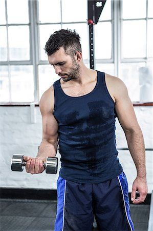 Fit man lifting heavy black dumbbells Stock Photo - Premium Royalty-Free, Code: 6109-08397794
