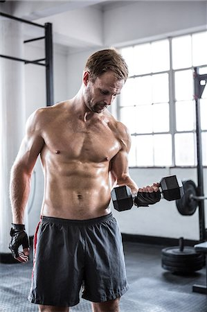 Fit man lifting heavy black dumbbell Stock Photo - Premium Royalty-Free, Code: 6109-08397854