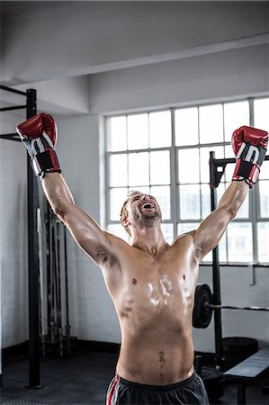 Fit man cheering with boxing gloves Stock Photo - Premium Royalty-Free, Code: 6109-08397864