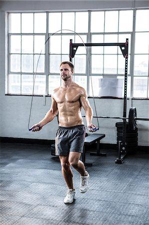 Fit man using skipping rope Stock Photo - Premium Royalty-Free, Code: 6109-08397871