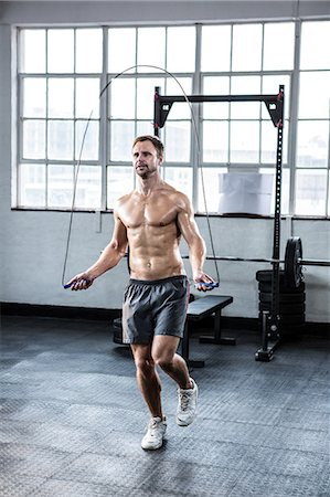 Fit man using skipping rope Stock Photo - Premium Royalty-Free, Code: 6109-08397871
