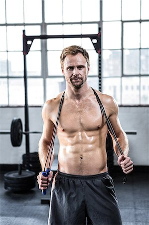 Fit man using skipping rope Stock Photo - Premium Royalty-Free, Code: 6109-08397872