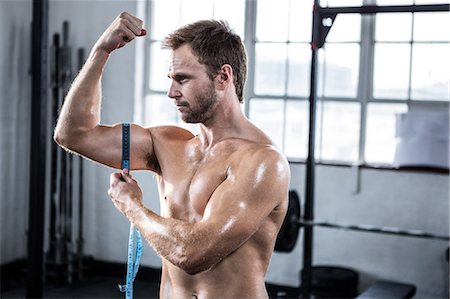 physical fitness - Fit man measuring his bicep Stock Photo - Premium Royalty-Free, Code: 6109-08397874