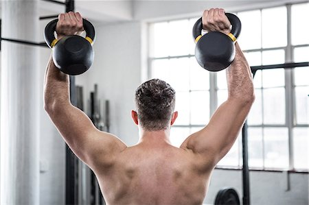 Fit shirtless man working out with kettlebells Stock Photo - Premium Royalty-Free, Code: 6109-08397823