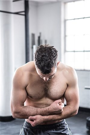 Fit man flexing his biceps Stock Photo - Premium Royalty-Free, Code: 6109-08397820