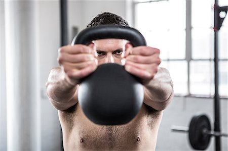 Fit shirtless man working out with kettlebell Stock Photo - Premium Royalty-Free, Code: 6109-08397821