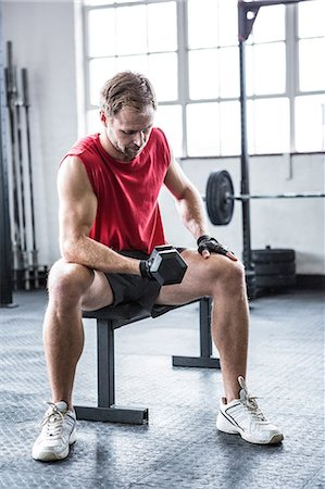 Fit man lifting heavy black dumbbell Stock Photo - Premium Royalty-Free, Code: 6109-08397835