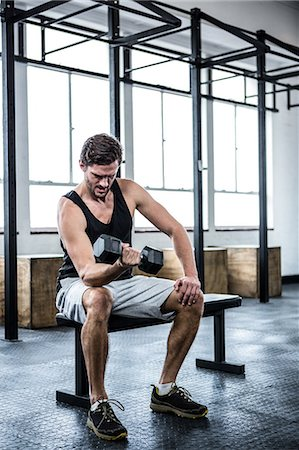 Fit man lifting heavy black dumbbell Stock Photo - Premium Royalty-Free, Code: 6109-08397995