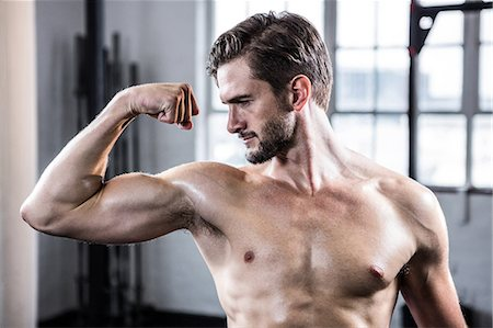 Fit shirtless man flexing his bicep Stock Photo - Premium Royalty-Free, Code: 6109-08398045