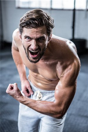 Fit shirtless man shouting and flexing Stock Photo - Premium Royalty-Free, Code: 6109-08398054