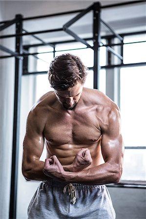 Fit shirtless man flexing his biceps Stock Photo - Premium Royalty-Free, Code: 6109-08398056