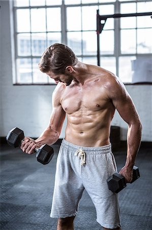 Fit shirtless man lifting dumbbells Stock Photo - Premium Royalty-Free, Code: 6109-08398060